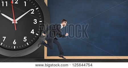 Geeky young businessman running mid air in front of a clock and a chalkboard