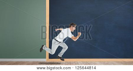 Geeky happy businessman running mid air in front of a chalkboard