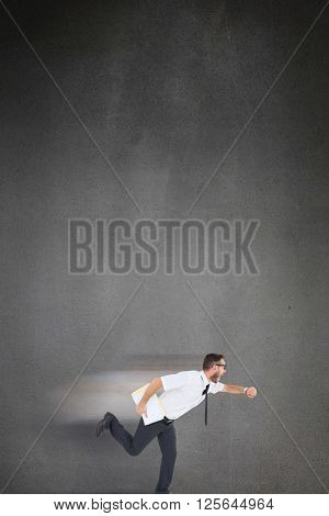 Geeky young businessman running late on black background
