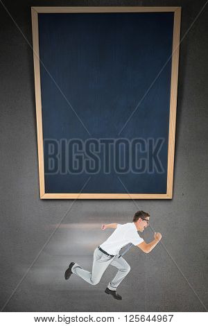Geeky happy businessman running mid air on grey background with black board