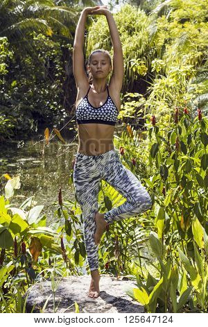 Yoga woman poses in tropics wearing stylish sportswear. Phuket, Thailand
