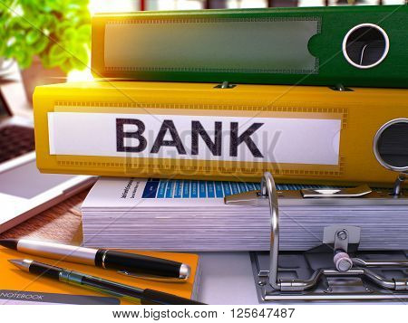 Yellow Ring Binder with Inscription Bank on Background of Working Table with Office Supplies and Laptop. Bank - Toned Illustration. Bank Business Concept on Blurred Background. 3D Render.