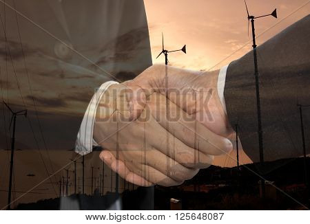 Double exposure business man handshake and wind energy industry concept.