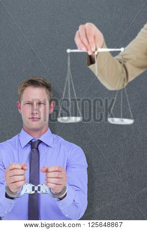 Young woman holding scales of justice and a gavel against grey background