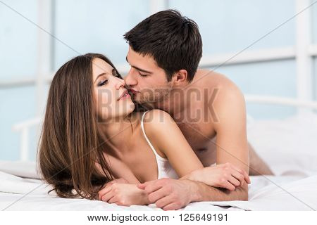 Loving couple in bed. Beautiful young loving couple lying in bed, kissing and looking to each other