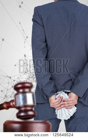 Rear view of businessman with handcuff and banknotes against black lines on grey background