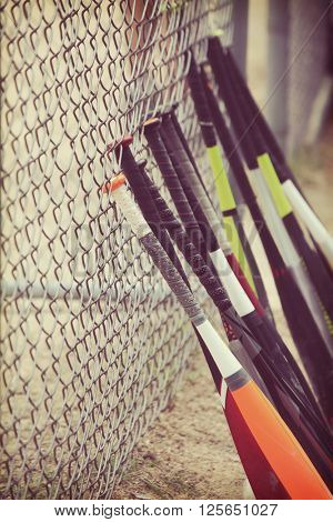 Youth baseball bats lined up against a chain link fence in batting cage