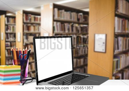 Open laptop against close up of a bookshelf