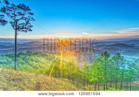 Early on a sunny plateau Dalat with rays radiating from horizon, beneath  rolling mountains in mist covered pine forest warm welcome new day in mountains Vietnam