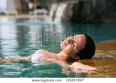 Beautiful woman enjoying summer in the pool