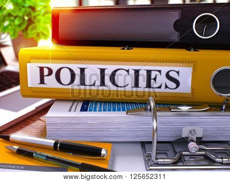 Yellow Ring Binder with Inscription Policies on Background of Working Table with Office Supplies and Laptop. Policies - Toned Illustration. Policies Business Concept on Blurred Background. 3D Render.