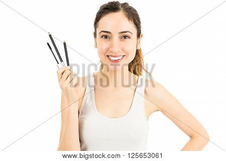 Caucasian smiling friendly make up woman holding and hsowing her make up equipment. Isolated on white background.