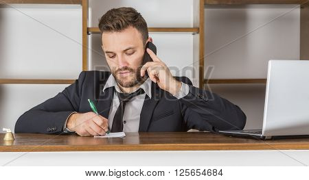 Portrait of a receptionist taking notice on a piece of paper while he is on the phone at his desk in a small hostel.