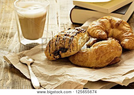 Caffe latte and croissant on wooden background.