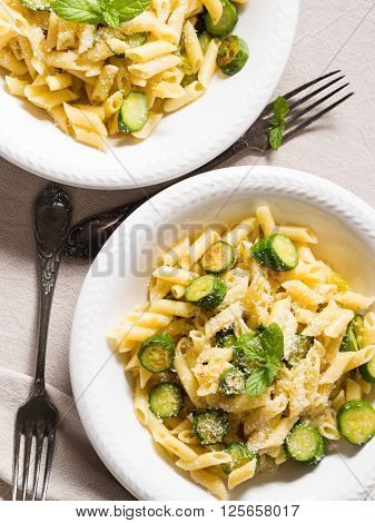 Pennette pasta with zucchini, fresh mint and grated parmesan cheese on beige table cloth, vertical shot