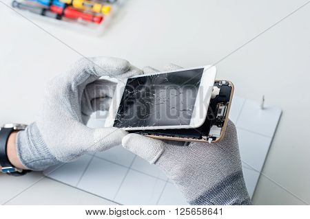 Close-up photos showing process of mobile phone repair, changing the screen.