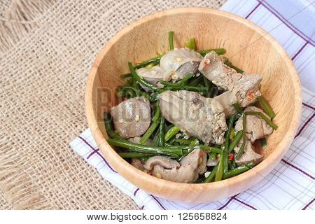 Stir Fried Pork Liver With Chinese Chives Flower And Garlic On Wood Bowl