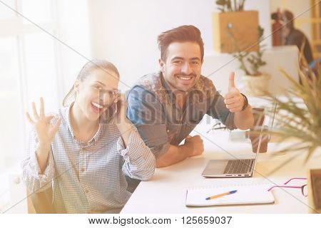 Happy freelance man and woman showing thumb-up and okay signs in office interior. Happy people working on laptop computer upon business projects.