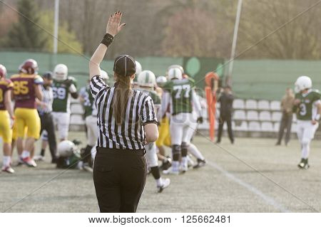 Female American football referee giving signals and blurred players in the background