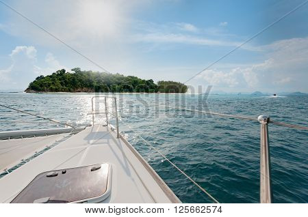 Private catamaran boat sailing to the island ahead. Luxury Lifestyle. Traveling on a yacht ** Note: Visible grain at 100%, best at smaller sizes