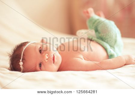 Cute baby girl lying in bed closeup. Good morning, Looking at camera. Childhood.