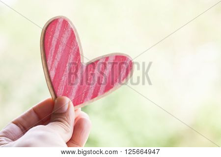hand holding wooden pink heart on a green pastel background