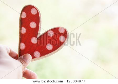 hand holding red polka dot wooden background