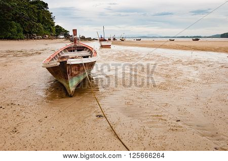 Abandoned old wooden wreck boat on the beach in Phuket Thaialnd