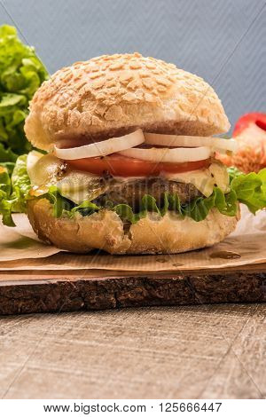 Homemade vegetarian burgers with fresh organic vegetables on rustic wooden background