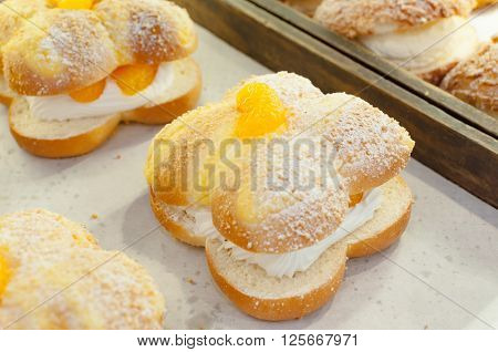 Choux cream sweet with orange on top in a bakery shop Bangkok Thailand