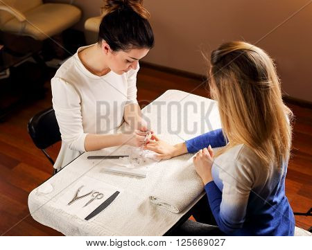 Beautiful blonde girl on reception at the manicurist in salon is making manicure