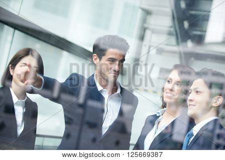 business people group meeting and pointing something in front of the office window . asian people & european
