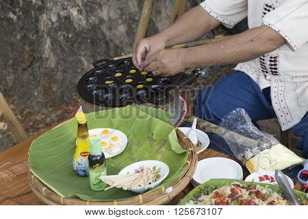 CHIANG MAI, THAILAND - APRIL 13: The man making grilled quail egg snack for sale at the ancient lanna house 140 years in water festival in Chiang Mai Thailand on April 13 2016.