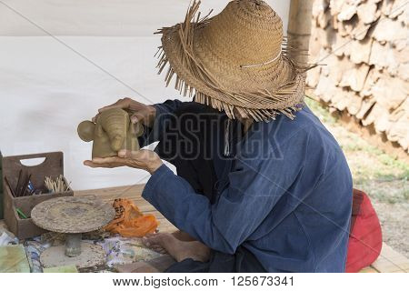 Man Molding Elephant Clay Figurine