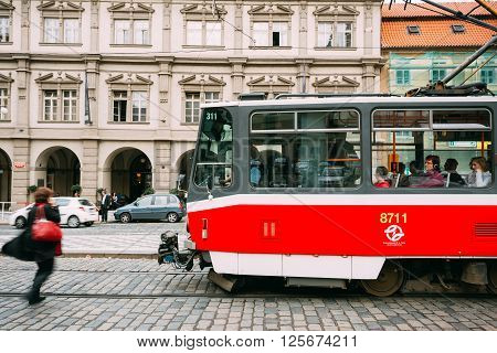 Prague, Czech Republic - October 10, 2014: People cross the tram tracks on the street Malostranske namesti