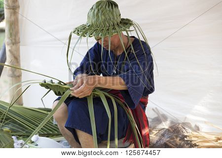 CHIANG MAI, THAILAND - APRIL 13: artisan weaving palm leaf for making hat at the ancient lanna house 140 years in water festival in Chiang Mai Thailand on April 13 2016.