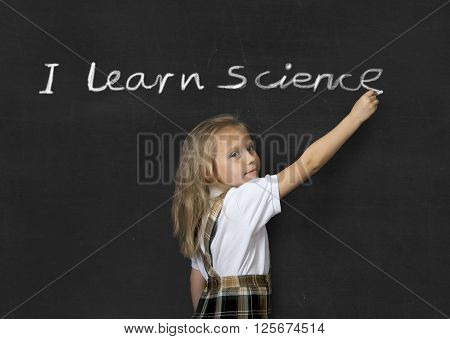 young sweet junior schoolgirl with blonde hair standing happy writing with chalk on classroom blackboard I learn Science text in children learning at school and education concept