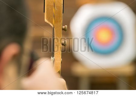 Archer aiming against the blurred target. Close up view ** Note: Shallow depth of field