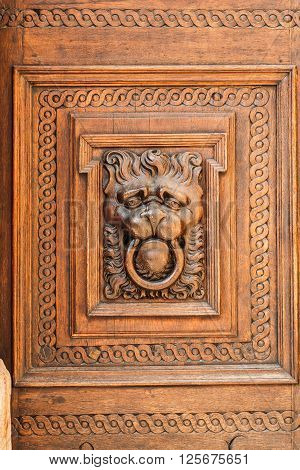 Lion head wood carving on old wooden door. Decorate detail. Old town Hall in Prague