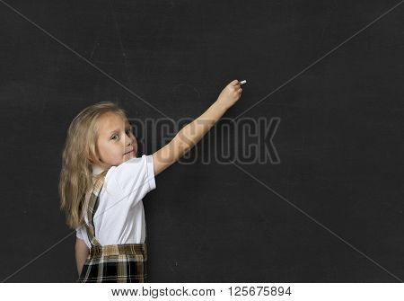 young sweet junior schoolgirl with blonde hair standing happy and smiling writing with chalk isolated in front of school classroom blackboard wearing school uniform in children education