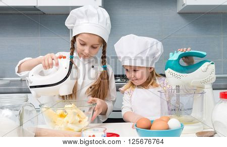 two funny little girls in chef uniform with ingredients on kitchen table