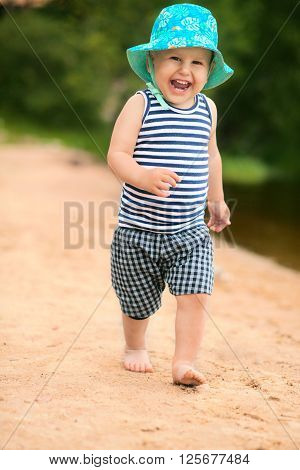 Cute baby running on the beach outdoors