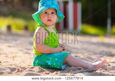 Cute baby sitting on the sand, outdoors