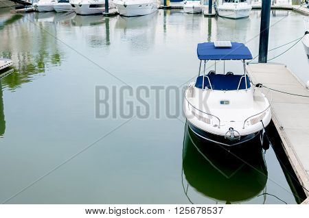 Small white motorboat docking at a harbour at Phuket Thailand