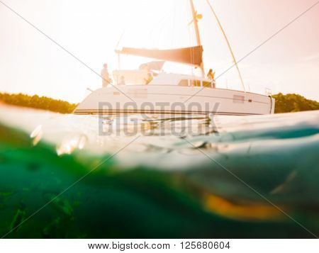 Semi Underwater blur Scene of tropical Island Yacht Reef with small fishes and swimmers Phuket