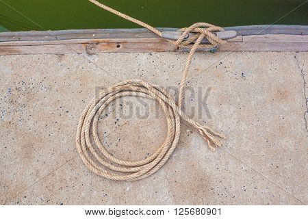 Boat docking point at a marina - rope fixed around a belay in a small harbor
