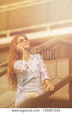Smiling businesswoman talking over mobile phone with her collegues. Long-haired girl in sunglasses looking up and posing near office building.