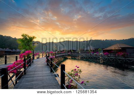 Overwater bungalow at dusk.Beautiful sunset over beach with water villas in luxury resort.Summer vacation concept