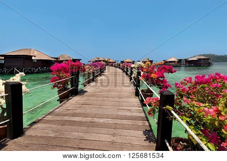 Overwater bungalows and wooden jetty.Beautiful view of water villas in resort.Summer vacation concept