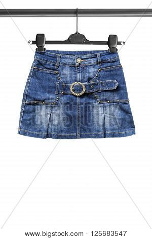 Blue denim mini skirt on clothes rack isolated over white